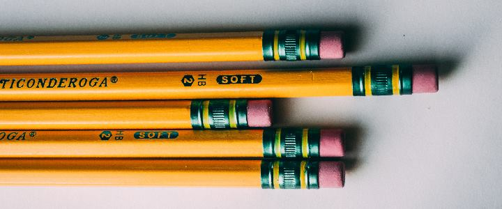The ends of five pencils with erasers.