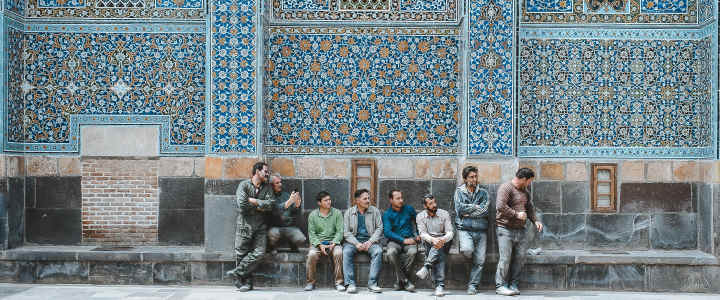 A group of people sitting in front of a wall mosaic.