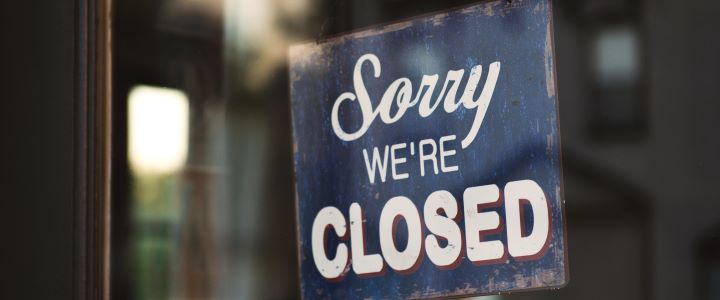 """Sign hanging in a door frame: """"Sorry, we're closed."""""""
